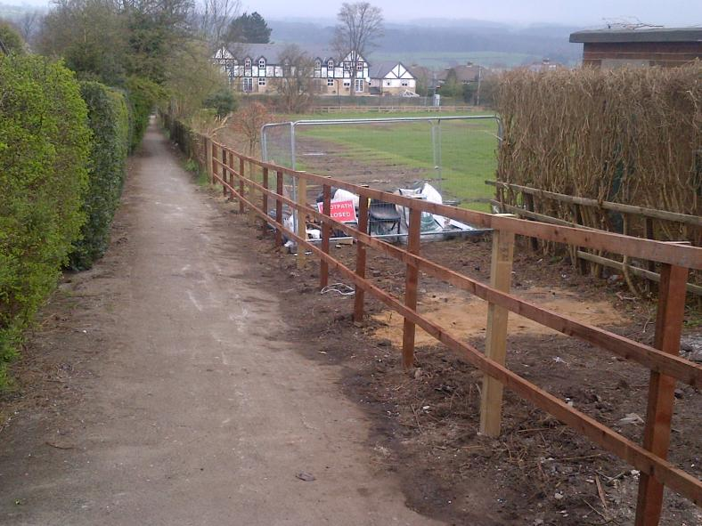 Timber fence replaced and small site compound remains until the gate is installed.