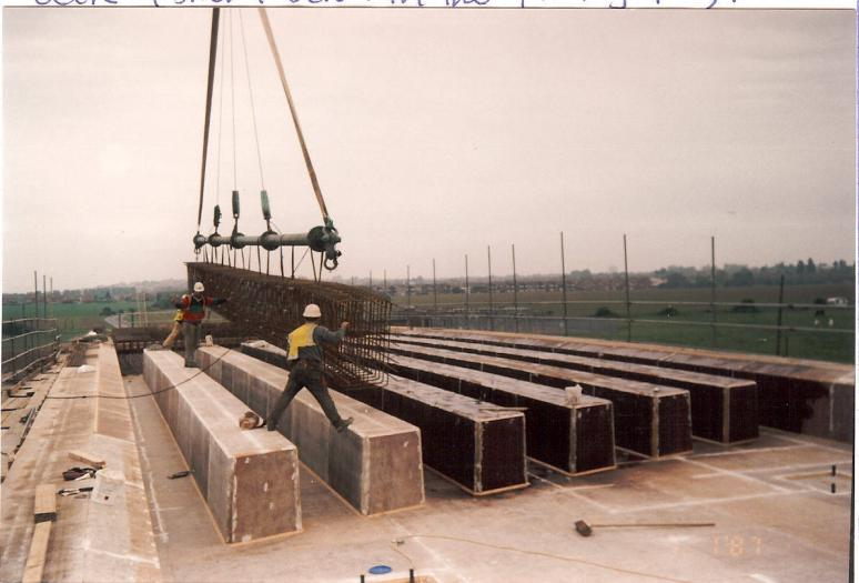 Steel reinforcement being lifted in between void formers on the deck.