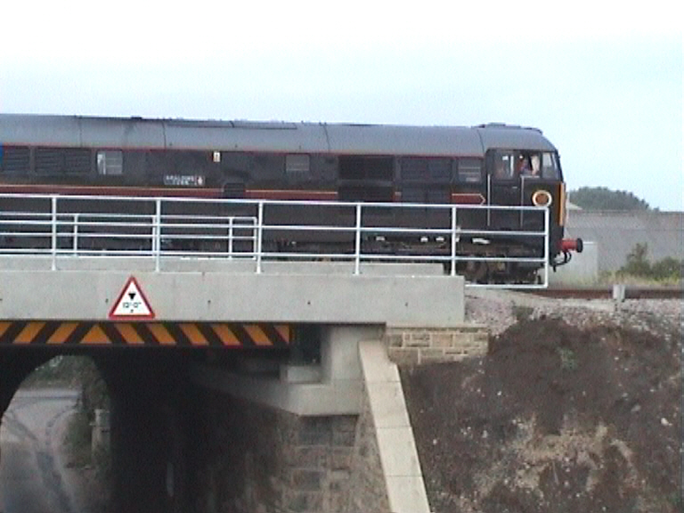 Train running over the bridge. New parapets installed.